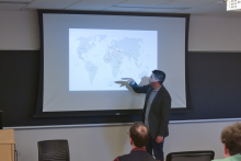 Peter Tinti using a world map to address the impact of profits of hope on the modern world