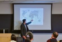 Peter Tinti showing a map of the world during his talk about migrant smugglers