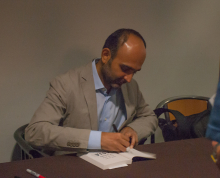 Mohsin Hamid signing one of his books - Lehigh University